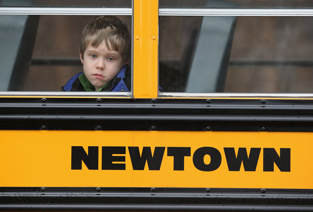 . A child gazes from a school bus as it passes by the St. Rose of Lima Catholic church while mourners gathered for a funeral service for shooting victim Jessica Rekos, 6, on December 18, 2012 in Newtown, Connecticut. Four days after 20 children and six adults were killed at Sandy Hook Elementary School, most students in Newtown returned to school. Children at Sandy Hook Elementary will attend a school in a neighboring town until authorities decide whether or not to reopen their school.  (Photo by John Moore/Getty Images)