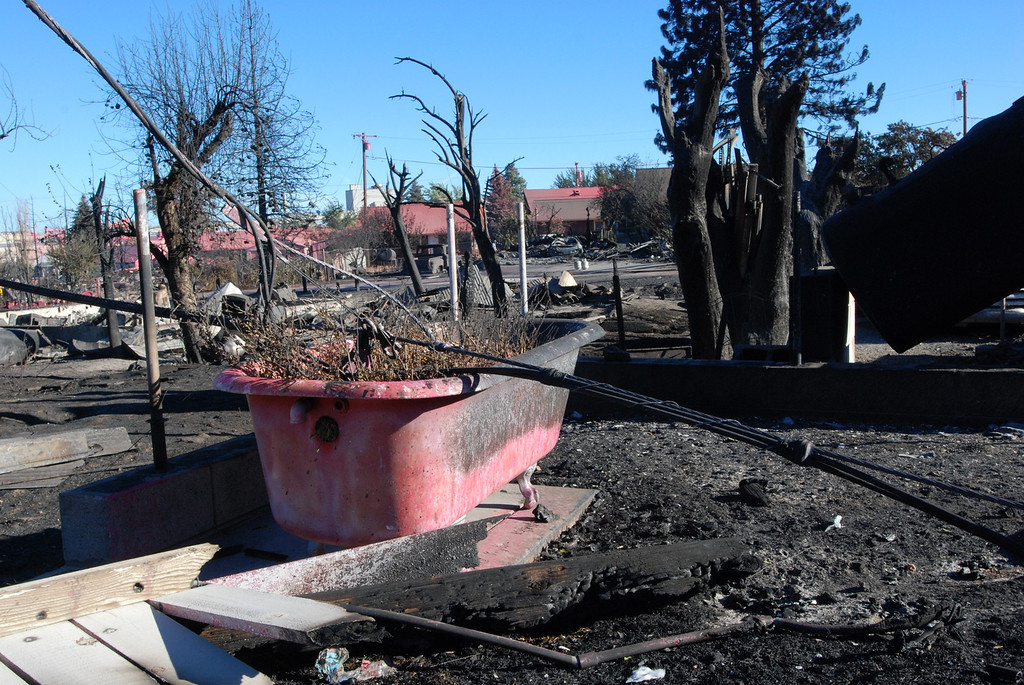 . A bathtub is seen painted pink with fire retardant, Tuesday, Sept. 16, 2014, in the rubble of a home destroyed by a wildfire in Weed, Calif. The fast-moving fire leveled approximately 100 structures. (AP Photo/Jeff Barnard)
