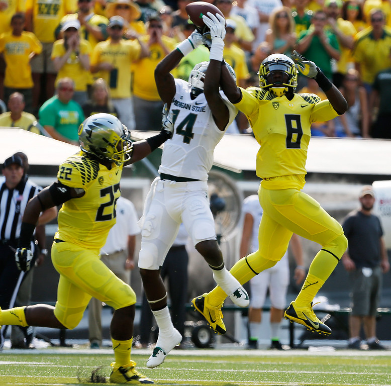 . CORRECTS NAME OF MICHIGAN PLAYER TO TONY LIPPETT - Oregon\'s Derrick Malone Jr., left, and Reggie Daniels, right, double team Michigan State\'s Chris Laneaux, center, to force an incomplete pass during the first quarter of their  NCAA college football game in Eugene, Oregon, Saturday Sept. 6, 2014. (AP Photo/Chris Pietsch)