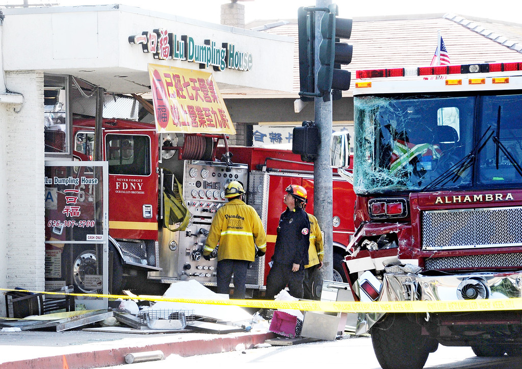 . Emergency personnel investigate the scene where a fire crashed into Lu Dumpling House restaurant after it two fire engines, one from Monterey Park and Alhambra Fire collided with  at the intersection of Emerson Avenue and Garfield Avenue in Monterey Park on Wednesday, April 16, 2014. (Photo by Walt Mancini/ Pasadena Star-News)