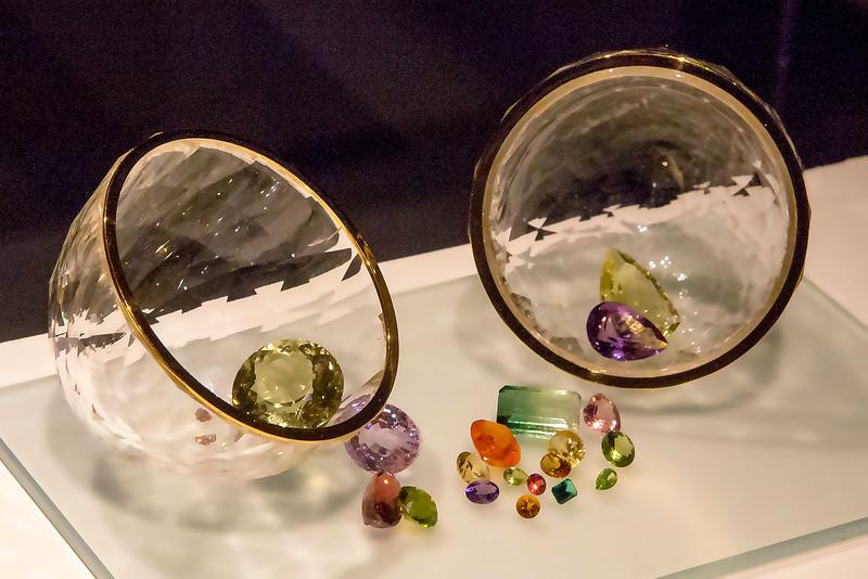 A quartz crystal sphere holding gemstones