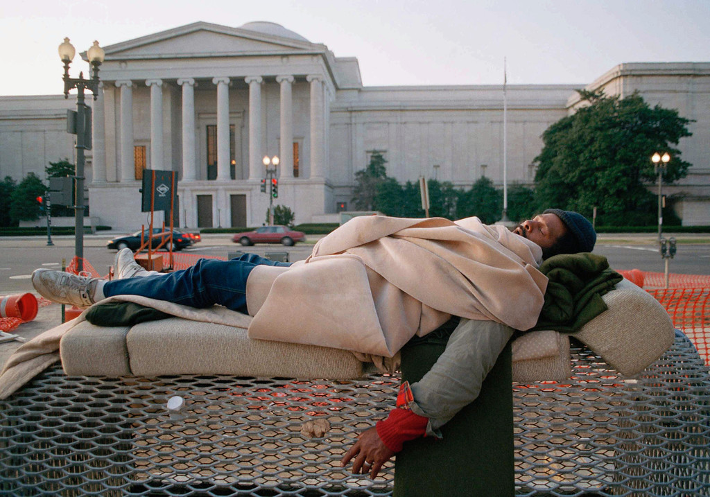 . A homeless man sleeps on a steam vent in front of the National Gallery of Art at 600 Pennsylvania Avenue in Washington on Jan. 19, 1993. President-Elect Clinton moved into the White House on the 20th, a mere 10 blocks away at 1600 Pennsylvania Avenue. (AP Photo/Mark Lennihan)