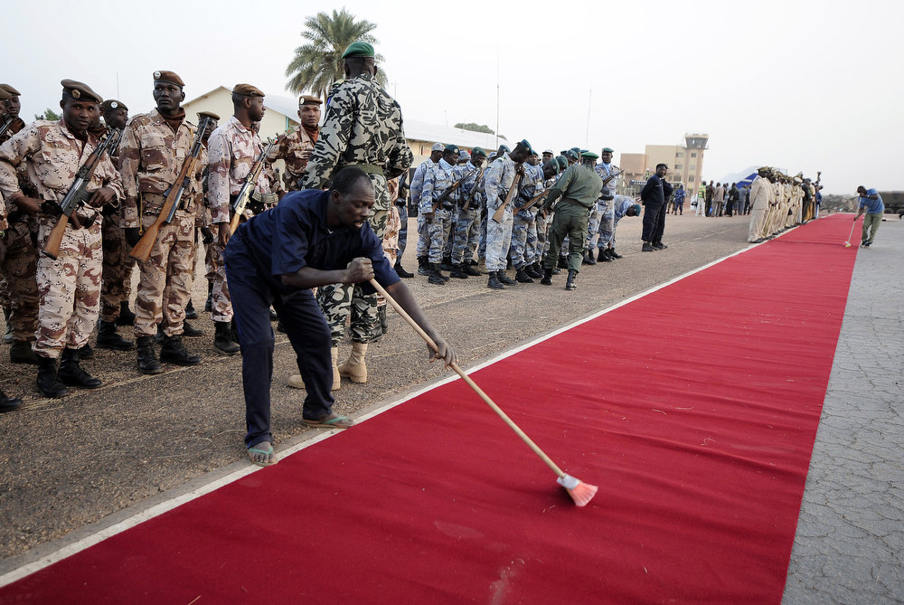 . A man sweeps the red carpet before the arrival of France\'s President and Mali\'s interim President at the Mopti airport, in Sevare, on February 2, 2013. President Francois Hollande visits today Mali as French-led troops work to secure the last Islamist stronghold in the north after a lightning offensive against the extremists. PASCAL GUYOT/AFP/Getty Images
