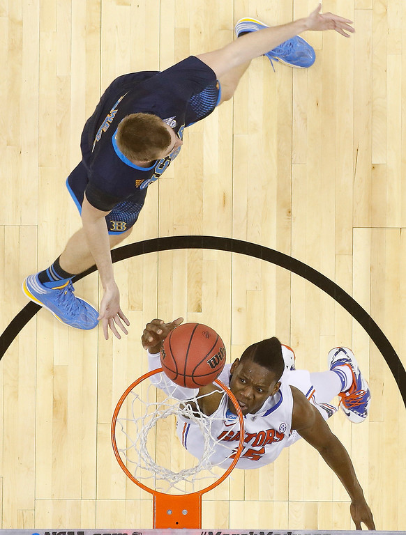. Florida forward Will Yeguete (15) shoots against UCLA forward David Wear (12) during the first half in a regional semifinal game at the NCAA college basketball tournament, Thursday, March 27, 2014, in Memphis, Tenn. (AP Photo/John Bazemore)