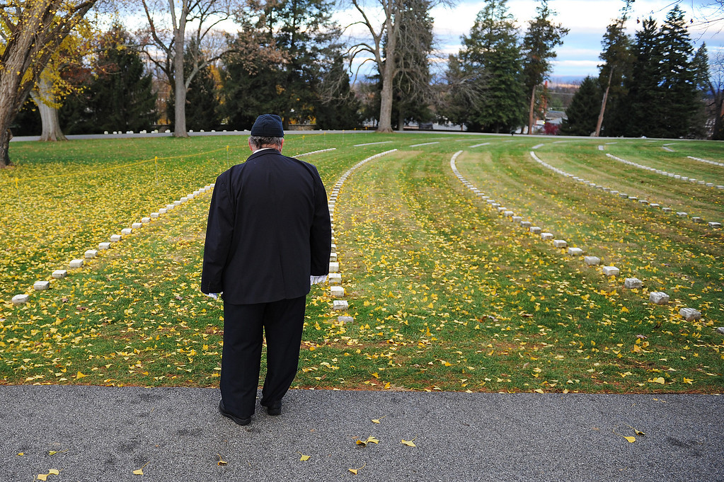 . A visitor looks at grave markers prior to a commemoration of the 150th Anniversary of the Gettysburg Address at the Soldiers\' National Cemetery at Gettysburg National Military Park on November 19, 2013 in Gettysburg, Pennsylvania. (Photo by Patrick Smith/Getty Images)