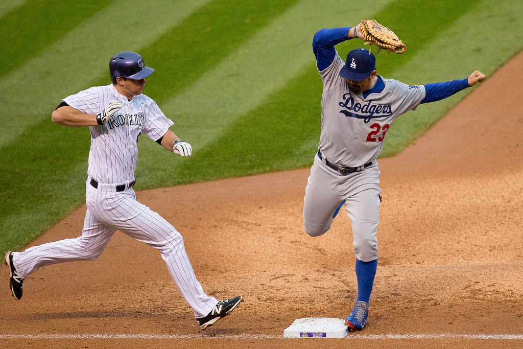 . First baseman Adrian Gonzalez #23 of the Los Angeles Dodgers touches first before DJ LeMahieu #9 of the Colorado Rockies for the second out of the fifth inning at Coors Field on June 8, 2014 in Denver, Colorado. (Photo by Justin Edmonds/Getty Images)