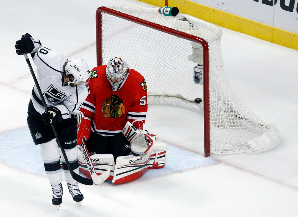 . Los Angeles Kings center Mike Richards (10) scores a goal on a deflection against Chicago Blackhawks goalie Corey Crawford (50) during the closing seconds of the third period in Game 5 of the NHL hockey Stanley Cup playoffs Western Conference finals, Saturday, June 8, 2013, in Chicago. (AP Photo/Charles Rex Arbogast)