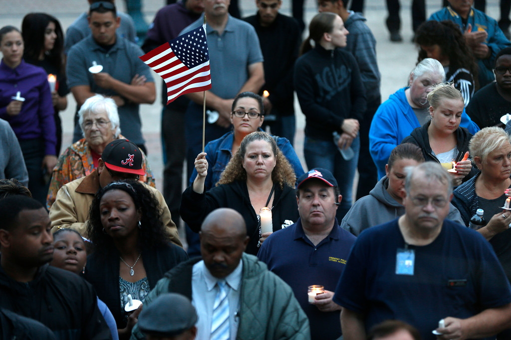. Some members of the community hold candles and American flags during a candlelight vigil for slain Hayward police Sgt. Scott Lunger at Hayward City Hall in Hayward, Calif., on Wednesday, July 22, 2015. Lunger was killed during a traffic stop early Wednesday. (Ray Chavez/Bay Area News Group)Lin