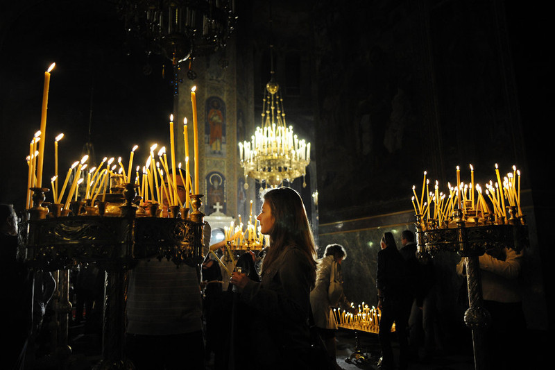 . A woman lights a candle during the Easter service at the golden-domed Alexander Nevski Cathedral in Sofia on May 05, 2013. The Bulgarian Orthodox Church celebrated Easter, according to the Julian calendar. DIMITAR DILKOFF/AFP/Getty Images