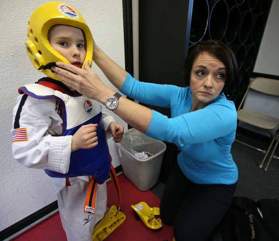 . Kim Rice helps her son Sammy Masek, 6, get his protective gear on during a martial arts class on Monday, Feb. 11, 2013 in Pleasanton, Calif.  Masek is one of a growing number of children that have lost their diagnosis of autisim.  (Aric Crabb/Staff)