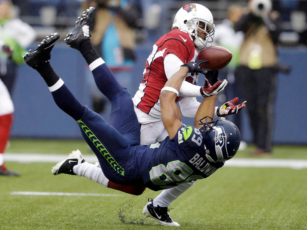 . Arizona Cardinals cornerback Jerraud Powers, top, breaks up a pass intended for Seattle Seahawks wide receiver Doug Baldwin in the second half of an NFL football game, Sunday, Dec. 22, 2013, in Seattle. (AP Photo/Elaine Thompson)