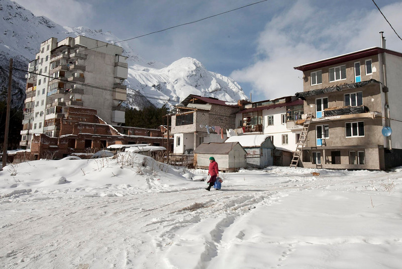 . A woman passes by residential houses in Prielbrusye near Mount Elbrus, February 2, 2013. These days only a handful of the most intrepid skiers and hikers make it to Elbrus, which dominates the North Caucasus region, where Islamist insurgents from ethnic minorities are fighting Russian rule and want to establish an Emirate. Elbrus is the unlikely centerpiece of a $26-billion Kremlin project for a chain of luxury mountain resorts that Moscow hopes will succeed, where guns and troops have not, in ending the violence and easing dissent in the region. Picture taken February 2, 2013. REUTERS/Kazbek Basayev