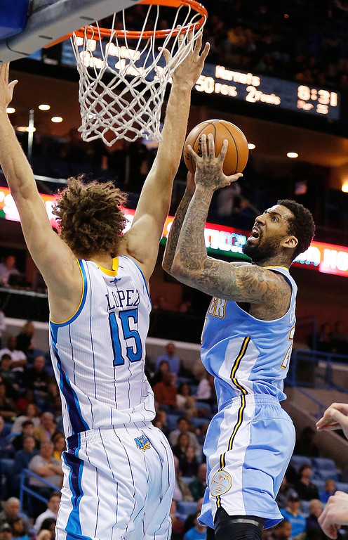 . Denver Nuggets guard Wilson Chandler (21) drives to the basket as New Orleans Hornets center Robin Lopez (15) defends in the second half of an NBA basketball game in New Orleans, Monday, March 25, 2013. The Hornets won 110-86. (AP Photo/Bill Haber)
