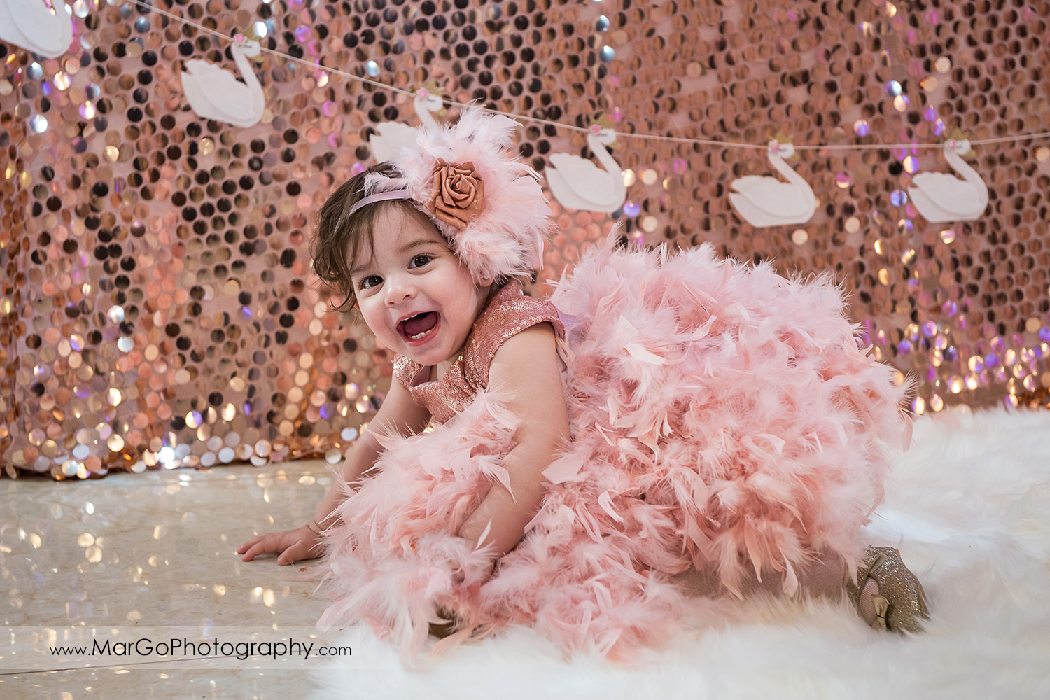 birthday girl in pink feather dress and flower and feather hair band on a pink and gold backdrop with white swans at Newark Oasis Palace