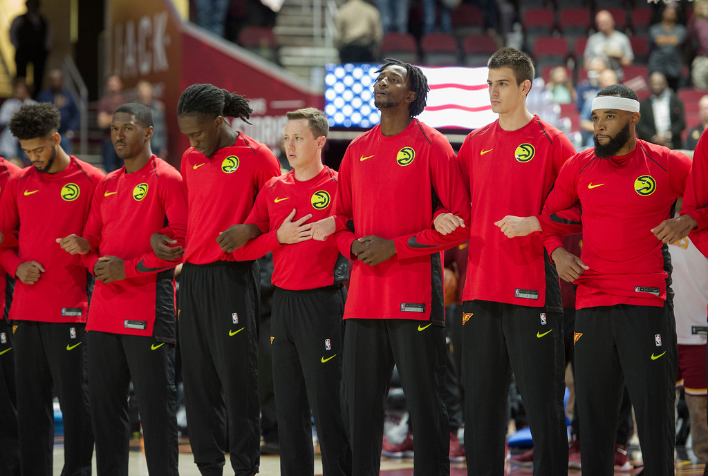 . Members of the Atlanta Hawks lock arms and listen to the national anthem before an NBA pre-season basketball game against the Cleveland Cavaliers in Cleveland, Wednesday, Oct. 4, 2017. (AP Photo/Phil Long)