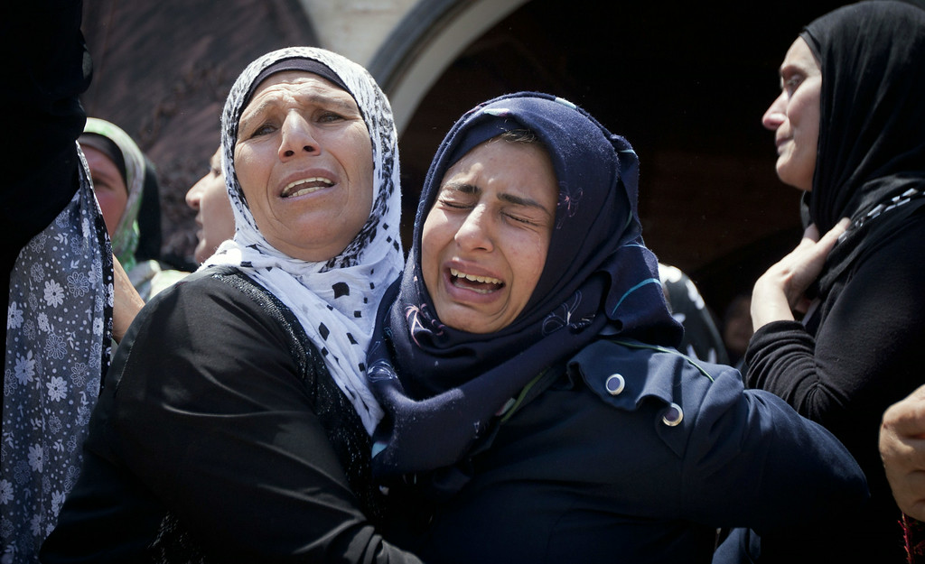 . A relative of Palestinian Mahmoud Shawamreh cries during his funeral in the West Bank village of Al-Ram, Tuesday, July 22, 2014. Shawamreh, 21, died after he was shot during clashes with Israeli troops Monday. (AP Photo/Majdi Mohammed)