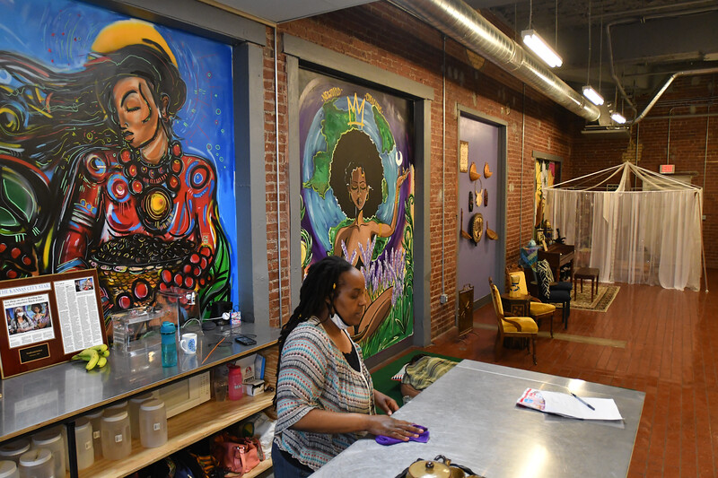 """Nika Cotton works inside Soulcentricitea on May 29, 2021. The cafe is filled with Afro-centric art and also has a """"tea tent"""" for events or quiet space."""