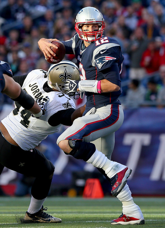 . Tom Brady #12 of the New England Patriots scrambles with the ball as  Cameron Jordan #94 of the New Orleans Saints defends at Gillette Stadium on October 13, 2013 in Foxboro, Massachusetts.  (Photo by Elsa/Getty Images)