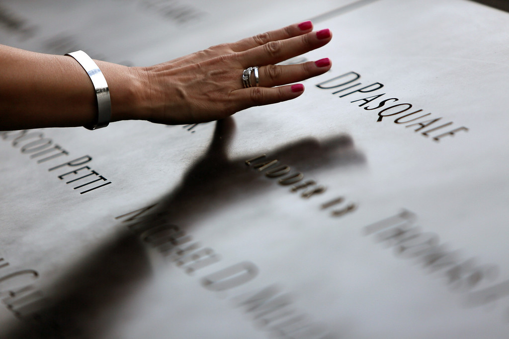 . A attendee touches a name at the 9/11 Memorial as they attend ceremonies for the twelfth anniversary of the terrorist attacks on lower Manhattan at the World Trade Center site on September 11, 2013 in New York City.   (Photo by Chris Pedota-Pool/Getty Images)