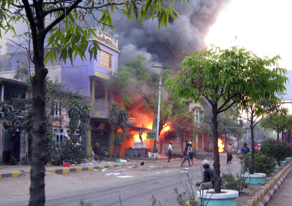 . In this Thursday, March. 21, 2013 photo, local residents walk on a road near a burning building following ethnic unrest between Buddhists and Muslims in Meikhtila, Mandalay division, about 550 kilometers (340 miles) north of Yangon, Myanmar.  (AP Photo)