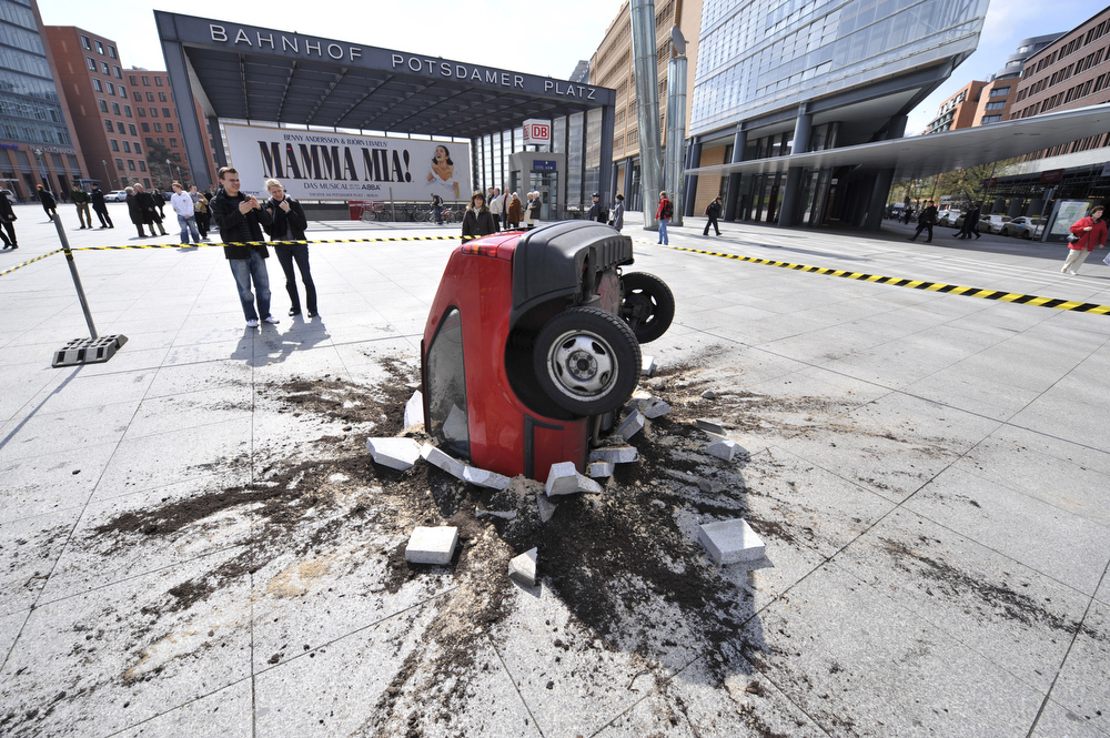 . A 3-D sculpture simulates a car crashed in the pavement on Berlin\'s Potsdamer Platz April 14, 2008. The sculpture is a publicity stunt for a German video-sharing site.     AFP PHOTO JOHN MACDOUGALL