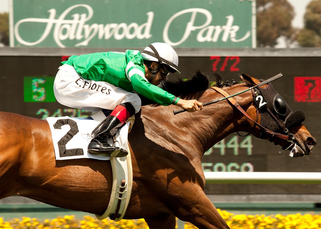 . FILE - In this July 4, 2011, file photo released by Benoit Photo, apprentice jockey Eswan Flores earns his first victory aboard a thoroughbred as he guides Kelly Leak to a one-length score in the fourth race at Hollywood Park in Inglewood Calif.  (AP Photo/Benoit Photo, File)