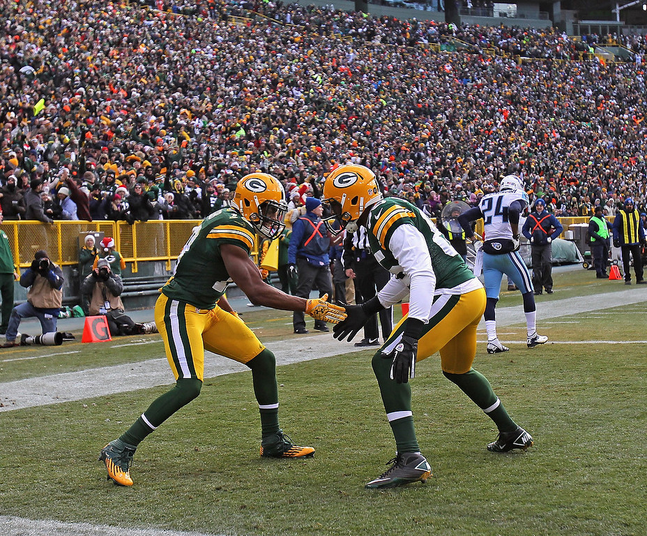 . Randall Cobb #18 of the Green Bay Packers (L) celebrates a touchdown catch with Greg Jennings #85 against the Tennessee Titans at Lambeau Field on December 23, 2012 in Green Bay, Wisconsin. The Packers defeated the Titans 55-7. (Photo by Jonathan Daniel/Getty Images)