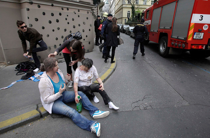 . Injured people sit on a sidewalk near the area of a blast after an explosion in Prague April 29, 2013. The explosion in central Prague on Monday injured about a dozen people and others were trapped in a building damaged by the blast, a Reuters witness and emergency services officials said.  REUTERS/David W Cerny