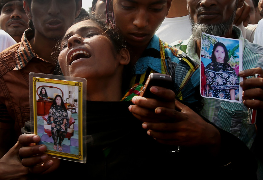 . A woman mourns as she arrived in hopes to find her sister, seen in the photograph she is holding, among unclaimed bodies brought to a cemetery from the garment factory building collapse in preparation for a mass burial on Wednesday May 1, 2013 in Dhaka, Bangladesh. (AP Photo/Wong Maye-E)
