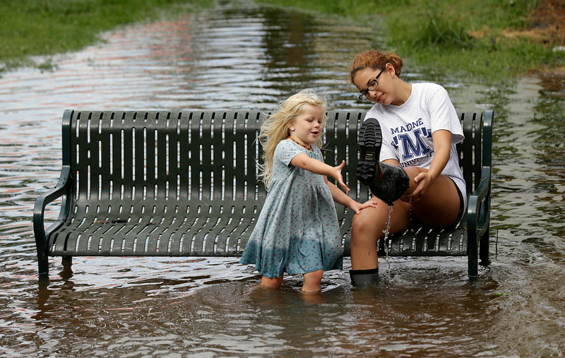 . Katie Bender gets some assistance from Johanna Bender, left, as they dump water from a boot while sitting on a flooded street after Hurricane Arthur passed through in Manteo, N.C., Friday, July 4, 2014. Arthur began moving offshore and away from North Carolina\'s Outer Banks early Friday after hitting the state\'s barrier islands overnight, creating a Fourth of July holiday that saw flooding and tens of thousands of power outages. (AP Photo/Gerry Broome)