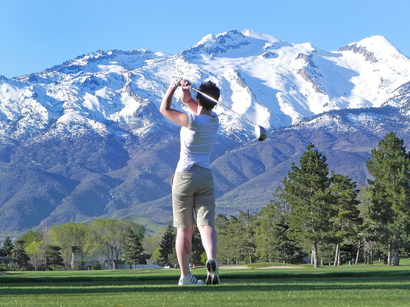 2011/5/13 A – It was Friday the 13th and I had two shots I liked but couldn't decide which I liked best so I'm posting both. This first shot is of Jessica hitting her second shot on the par 5 #2 hole at Alpine Country Club. I love how the mountains are so big and snow capped compared to the lush green grass. They emphasize the mountains. I lay down on my belly to take this shot.