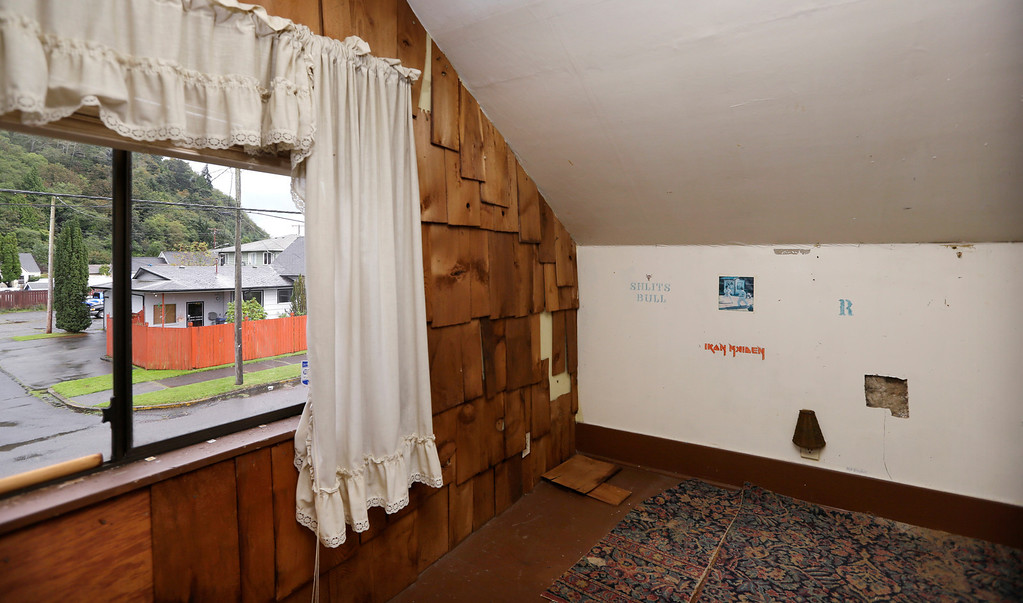 . In this photo taken Monday, Sept. 23, 2013, an attic bedroom used by Kurt Cobain, the late frontman of Nirvana,  still has the stencil-like logos of bands that he reportedly put on the walls, as well as the holes he put in them, at his childhood home in Aberdeen, Wash.  (AP Photo/Elaine Thompson)