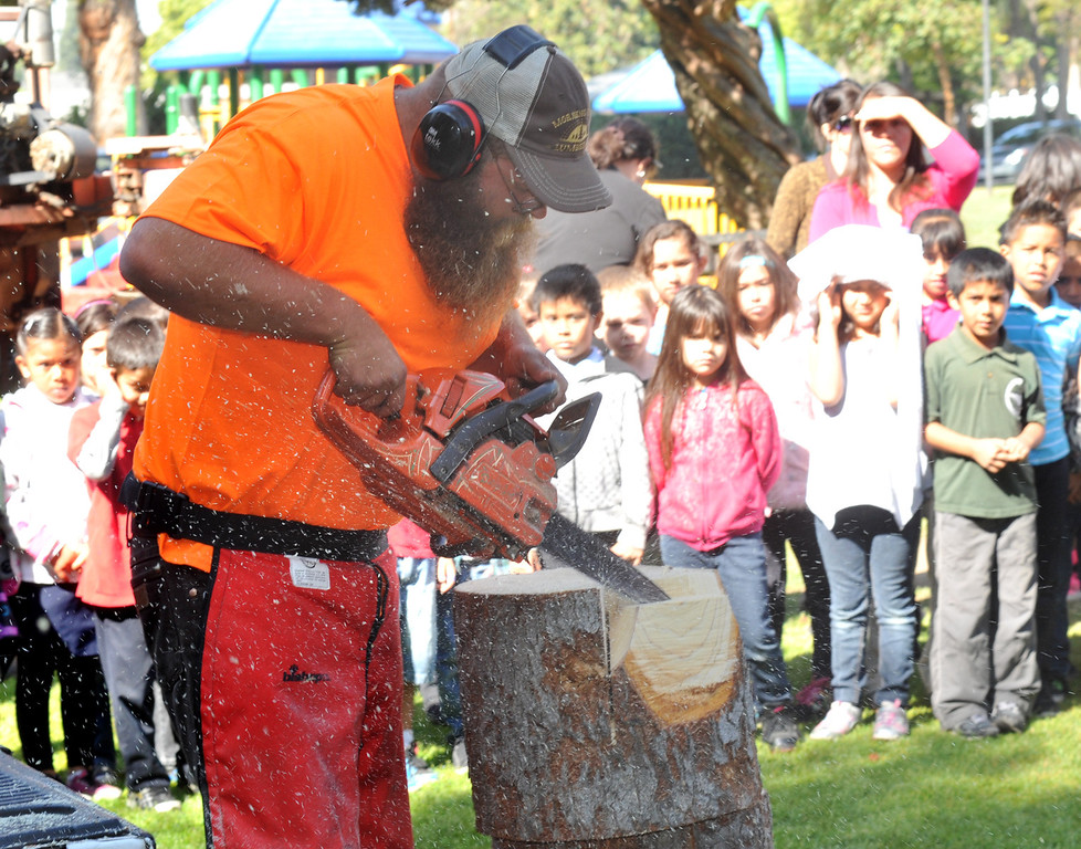. Wood carver John Mahoney decomstrates to students as they celebrate Arbor Day at Penn Park in Whittier on Thursday March 14, 2013. Student meet George Washington, assist in planting a tree and watch tree crews perform their tasks in the park.(SGVN/Staff Photo by Keith Durflinger)