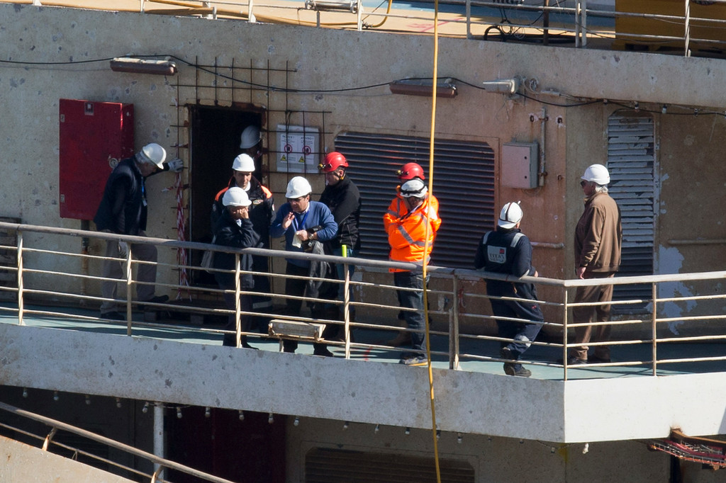 . Captain Francesco Schettino, fourth from left, talks on the upper deck of the wreck of the Costa Concordia cruise ship, just off the coast of the Giglio island, Thursday, Feb. 27, 2014. The captain of the Costa Concordia has been permitted to go aboard the shipwreck for the first time since it capsized two years ago as part of a new court-ordered search. Consumer groups and lawyers for Capt. Francesco Schettino asked the court in Grosseto to authorize the searches to determine if any factors beyond human error contributed to the disaster. After searching the bridge and elevators last month, experts will examine the emergency generators Thursday. (AP Photo/Andrew Medichini)