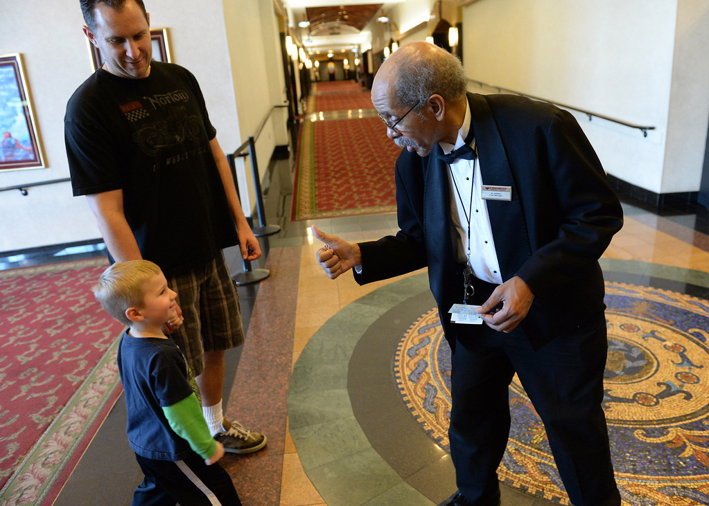 . Al Harris, floor manager of the Krikorian Premier Theatre, greets Ben Italiano, 4, of Redlands and his father Jimmy , before the start of their movie, Thursday, in Redlands,Ca., Feb. 13, 2014. Harris has become a local icon collecting tickets and giving high fives to moviegoers since being hired by Krikorian in 1992.  (John Valenzuela/Photographer)