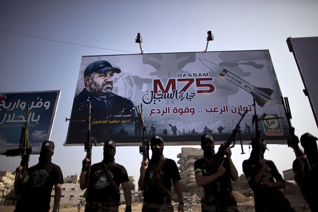 . Palestinian militants of the Ezzedine al-Qassam Brigades, Hamas\'s armed wing, stand in front of a billboard bearing a portrait of killed top Hamas military commander Ahmed Jaabari and a Gaza-made M75 rocket, during celebrations marking the first anniversary of an Israeli army operation which killed of Jaabari, on November 13, 2013 in Gaza City.  AFP PHOTO / MAHMUD HAMS/AFP/Getty Images