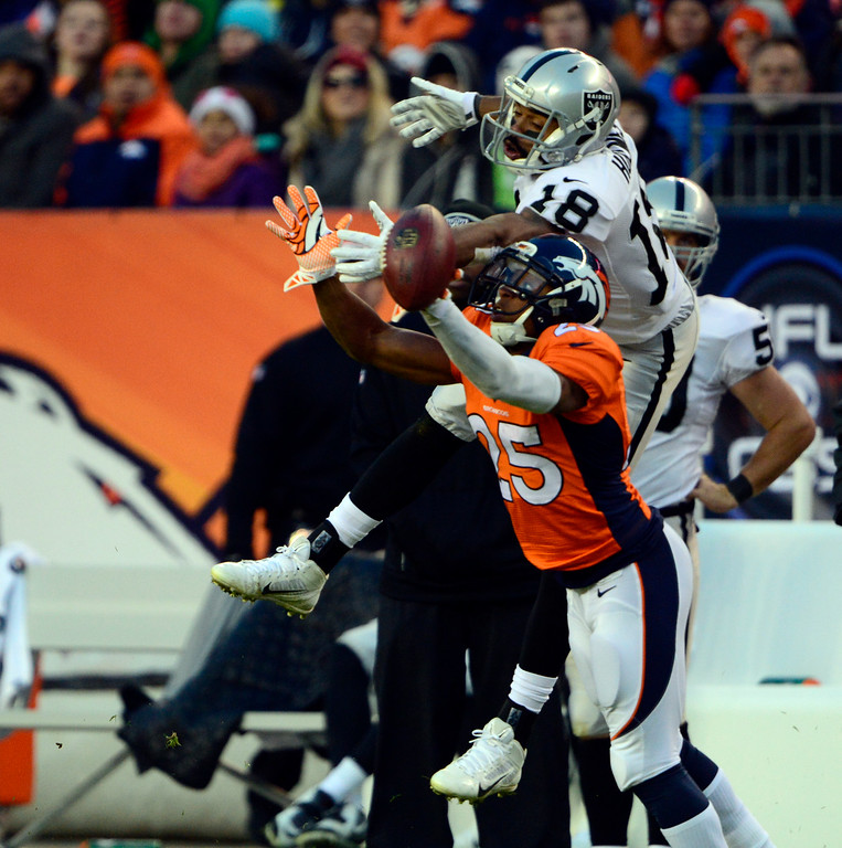 . DENVER, CO - DECEMBER 28: Chris Harris (25) of the Denver Broncos breaks up a pass intended for Andre Holmes (18) of the Oakland Raiders in the third quarter.  The Denver Broncos played the Oakland Raiders at Sports Authority Field at Mile High in Denver on December, 28 2014. (Photo by Joe Amon/The Denver Post)