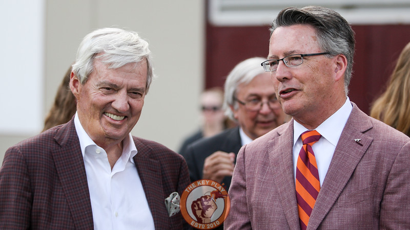 Former Virginia Tech head coach Frank Beamer (left) and Virginia Tech president Dr. Tim Sands (right) speak on the sidelines before the homecoming halftime ceremonies begin.  (Mark Umansky/TheKeyPlay.com)