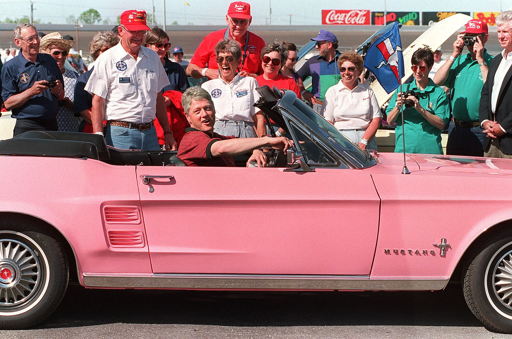 ". U.S. President Bill Clinton in a picture taken 17 April 1994 in Charlotte sits in a ""Playboy Pink\"" colored 1967 Ford Mustang owned by Bob and Rochelle McNeal (laughing, background) during a visit to Motor Speedway in Charlotte.  (Photo credit should read ROBERT GIROUX/AFP/Getty Images)"