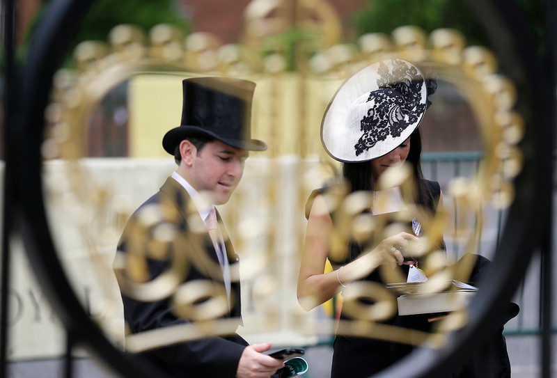 . Two race goers are viewed though a gold crown gate on the first day of the Royal Ascot horse race meeting in Ascot, England, Tuesday, June 18, 2013. (AP Photo/Alastair Grant)