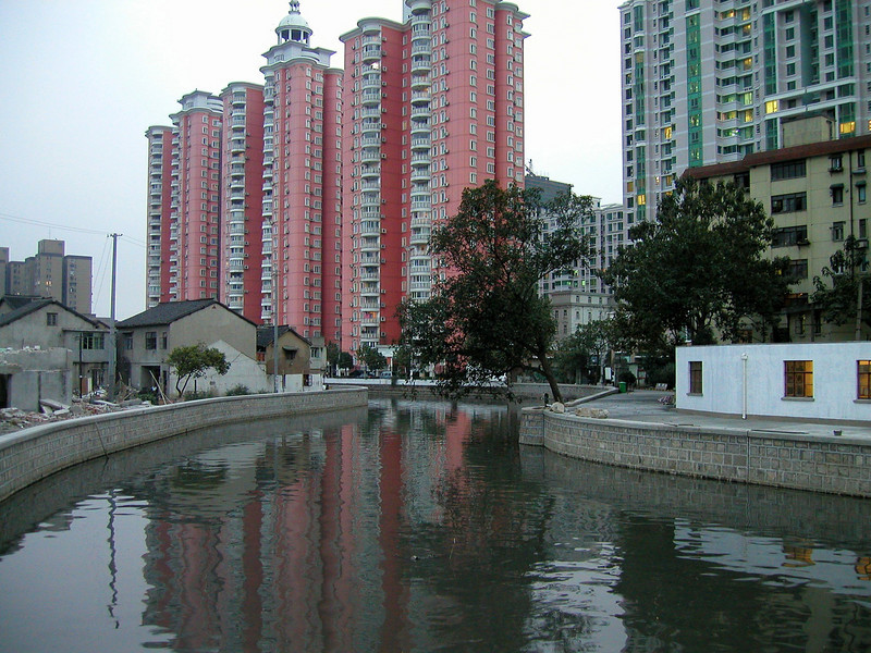 new apartments and a canal beside old homes under teardown.
