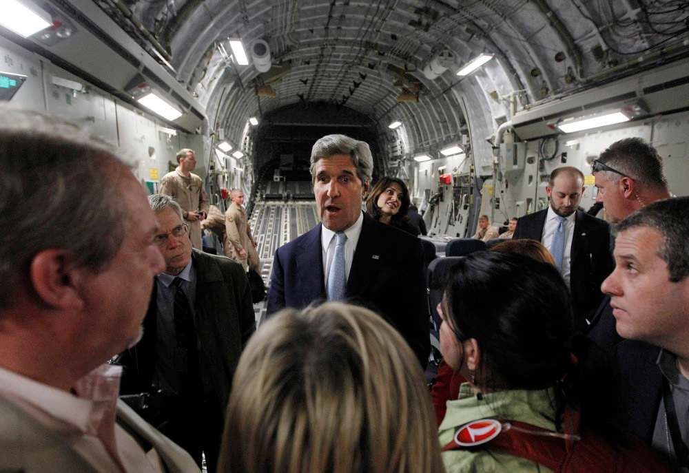 . U.S. Secretary of State John Kerry (C) speaks to the media on an Air Force C-17 aircraft upon his return to Amman from a trip to Baghdad March 24, 2013. Kerry made an unannounced visit to Iraq on Sunday and said he told Prime Minister Nuri al-Maliki of his concern about Iranian flights over Iraq carrying arms to Syria.  REUTERS/Jason Reed