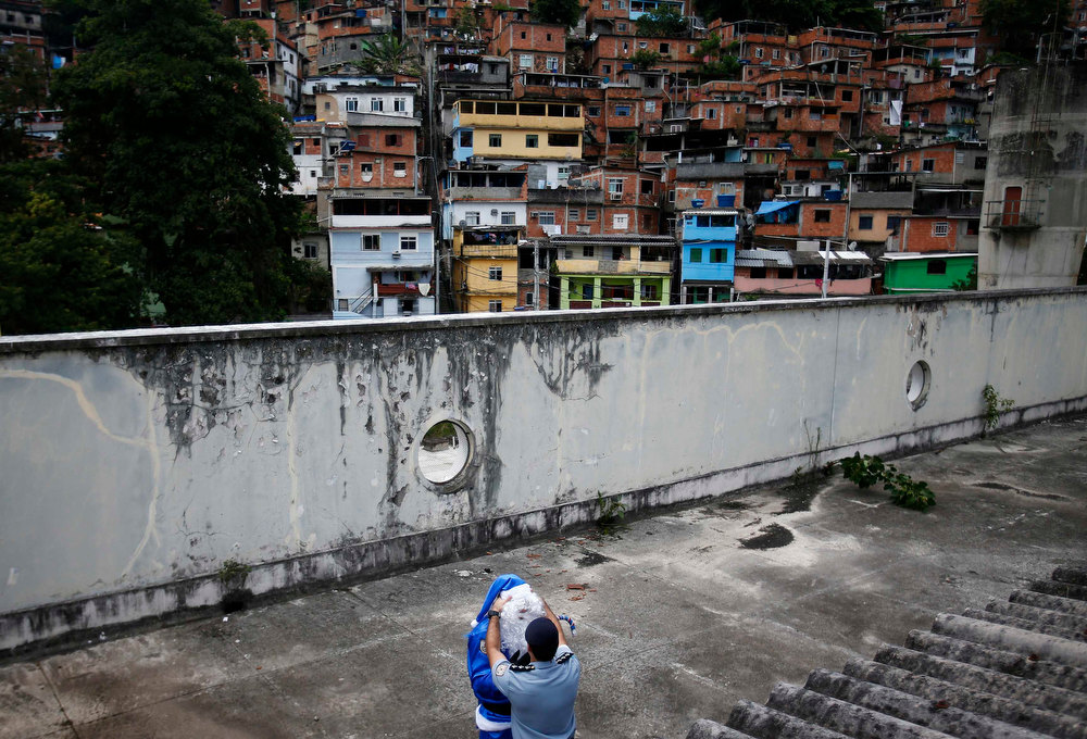 Description of . A policeman of the Peacekeeping Police Unit (UPP) gives the finishing touch to the costume of a colleague dressed up as Santa Claus in Rio de Janeiro's military police colours, before a Christmas party at Macacos slum in Rio de Janeiro December 20, 2012. REUTERS/Ricardo Moraes