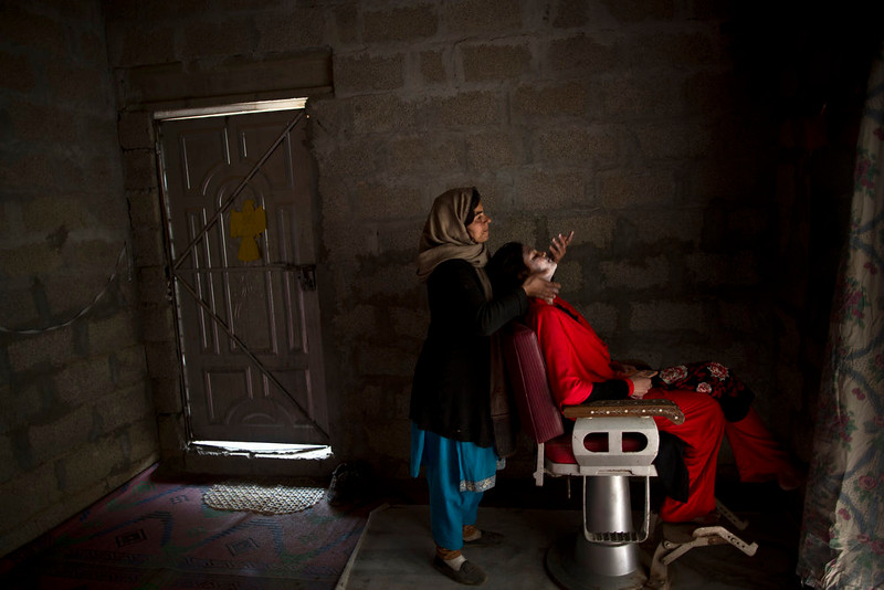 . Pakistani Christian Maria Akbar, 15, has her make up done by hairdresser Razia Rehmat, 39, in preparation for Christmas holiday, at a hair salon, in a slum that hosts Christian families, on the outskirts of Islamabad, Pakistan, Wednesday, Dec. 24, 2014. (AP Photo/Muhammed Muheisen)