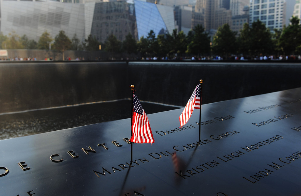 . Flags stand in a name on the 9/11 Memorial during ceremonies for the twelfth anniversary of the terrorist attacks on lower Manhattan at the World Trade Center site on September 11, 2013 in New York City. (Photo by David Handschuh-Pool/Getty Images)