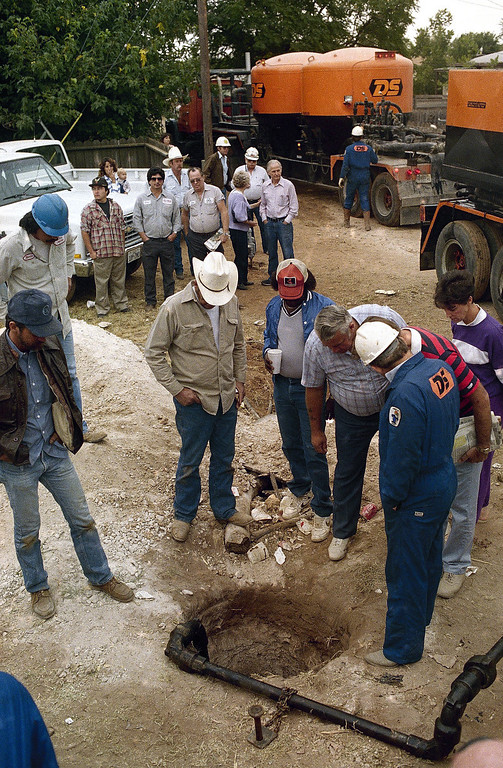 . Oil service workers and bystanders look over the 25-foot deep hole used to rescue 18-month-old Jessica McClure in Midland, Texas, as the hole is plugged with cement, Oct. 17, 1987. (AP Photo/Carlos Osorio)