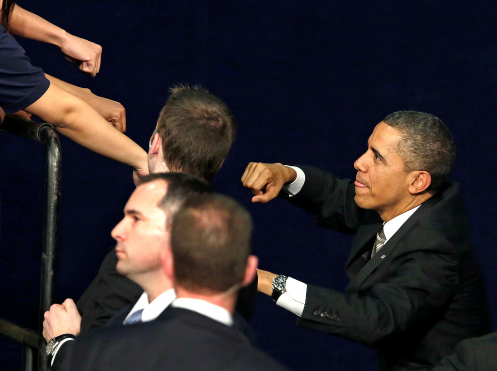 . President Barack Obama acknowledges the crowd as he exchanges fist bumps with the audience after speaking at Hyde Park Academy, Thursday, Feb. 14, 2013, in Chicago. (AP Photo/M. Spencer Green)