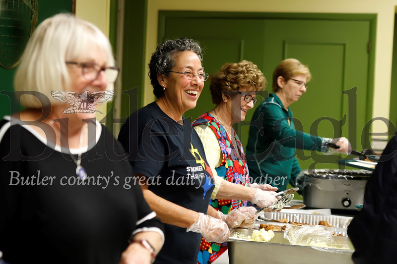Jo Renee Motko (left), Cindy Schmidt and other volunteers serve up community dinner at St. Paul Roman Catholic Church Tuesday night in Butler. Seb Foltz/Butler Eagle