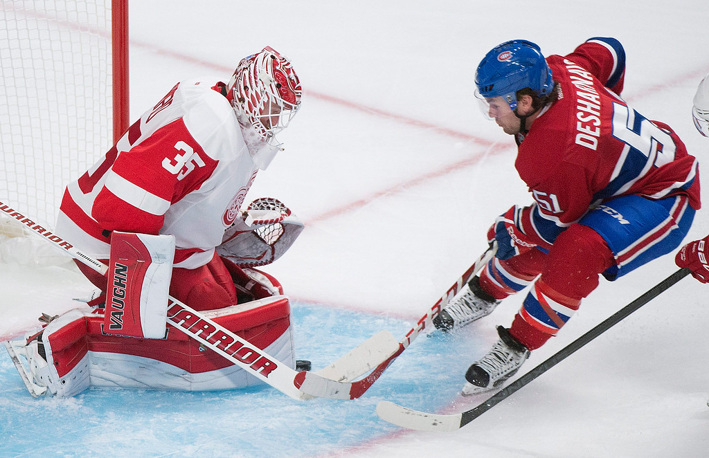 . Montreal Canadiens\' David Desharnais, right, slides in on Detroit Red Wings goaltender Jimmy Howard during third period NHL hockey action in Montreal, Tuesday, Oct. 21, 2014. (AP Photo/The Canadian Press, Graham Hughes)