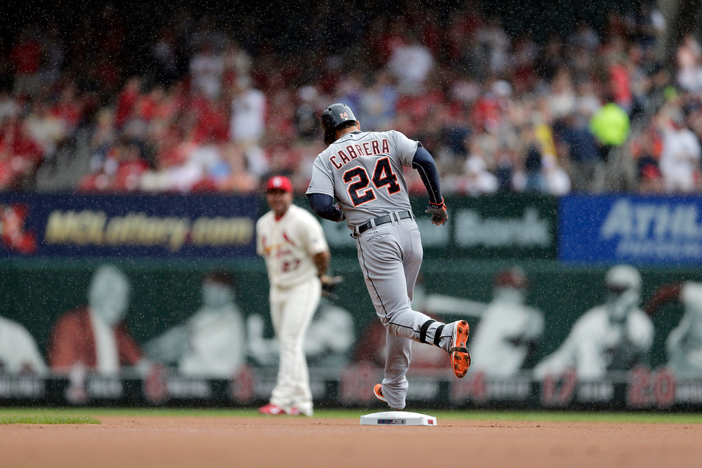 . Detroit Tigers\' Miguel Cabrera (24) rounds the bases in a light rain after hitting a solo home run as St. Louis Cardinals shortstop Jhonny Peralta watches during the first inning of a baseball game, Saturday, May 16, 2015, in St. Louis. (AP Photo/Jeff Roberson)